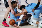 San Antonio Spurs' Lonnie Walker IV (1) scrambles for the ball with Memphis Grizzlies' De'Anthony Melton, left, and Dillon Brooks during the first half of an NBA basketball game Sunday, Aug. 2, 2020, in Lake Buena Vista, Fla. (AP Photo/Ashley Landis, Pool)