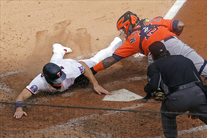 Minnesota Twins' Max Kepler, left, beats the tag by Houston Astros catcher Martin Maldonado to score on a Nelson Cruz's RBI double off Astros pitcher Zack Greinke in the third inning in Game 1 of an American League wild-card baseball series, Tuesday Sept. 29, 2020, in Minneapolis. (AP Photo/Jim Mone)