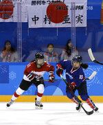 South Korea's Choi Jiyeon (10), of the combined Koreas team, skates with the puck against Haruna Yoneyama (10), of Japan, during the first period of the preliminary round of the women's hockey game at the 2018 Winter Olympics in Gangneung, South Korea, Wednesday, Feb. 14, 2018. (AP Photo/Matt Slocum)