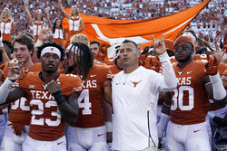 """In this Saturday, Sept. 4, 2021, file photo, Texas head coach Steve Sarkisian, center, joins players in singing """"The Eyes of Texas"""" after an NCAA college football against Louisiana-Lafayette, in Austin, Texas. The Texas chapter of the NAACP and a group of UT students have filed a federal civil rights complaint against the University of Texas for its continued use of """"The Eyes of Texas"""" school song, tune with racist elements in its past. The complaint filed Friday, Sept. 3, 2021, with the U.S. Department of Education alleges that Black students and faculty are being subjected to violations of the Civil Rights Act and a hostile campus environment. (AP Photo/Eric Gay)"""