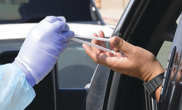 An Arizona Western College EMT Academy student hands a pair of straws to a participant in the drive-through COVID-19 saliva test on the main campus at Arizona Western College, in Yuma, Ariz., Saturday, Oct. 17, 2020. The straws are part of the testing kit. The testing, organized by the Yuma County Public Health Services District, lasted from 11 a.m. to 3 p.m., and saw 671 tests administered, according to Yuma County spokesperson Kevin Tunnell. The purpose of the testing, according to Yuma County, was to capitalize on the recent development of a saliva test for COVID-19 by Arizona State University's Biodesign Institute. The new test helps health officials achieve the goals of providing testing for all citizens that is simple and easy to use and is non-invasive, and to get a snapshot of the current infection rate in Yuma County. Health officials are asking everyone to get tested regardless of how they feel physically. (Randy Hoeft/The Yuma Sun via AP)