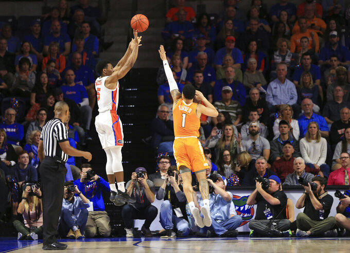Florida guard KeVaughn Allen (5) makes a 3-point shot over Tennessee guard Lamonte Turner (1) during the first half of an NCAA college basketball game Saturday, Jan. 12, 2019, in Gainesville, Fla. (AP Photo/Matt Stamey)