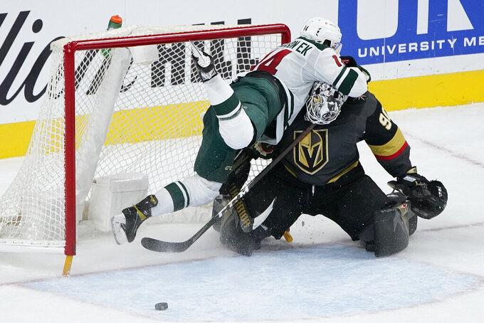 Minnesota Wild center Joel Eriksson Ek (14) falls into Vegas Golden Knights goaltender Robin Lehner (90) during overtime of an NHL hockey game Thursday, April 1, 2021, in Las Vegas. (AP Photo/John Locher)