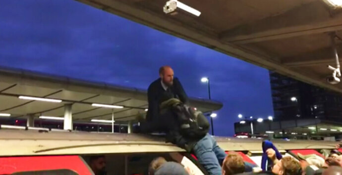 In this image taken from video, a man grabs a protester on top of a train, in London, Thursday Oct. 17, 2019. Angry commuters scuffled with climate activists who climbed onto the roofs of trains, snarling services in the busy morning rush hours in the British capital. (ITN via AP)
