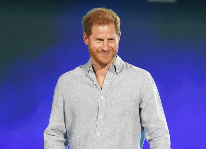 """FILE - Prince Harry, Duke of Sussex speaks at """"Vax Live: The Concert to Reunite the World"""" in Inglewood, Calif. on May 2, 2021. Prince Harry compared his royal experience to being on """"The Truman Show"""" and """"living in a zoo."""" The Dutch of Sussex said he contemplated quitting royal life on several occasions during his 20s in a Thursday episode of the """"Armchair Expert"""" podcast. (Photo by Jordan Strauss/Invision/AP, File)"""
