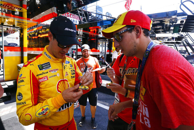 Driver Joey Logano signs autographs as he walks through the pits before practice for a NASCAR Cup Series auto race, Friday, Aug. 16, 2019, in Bristol, Tenn. (AP Photo/Wade Payne)