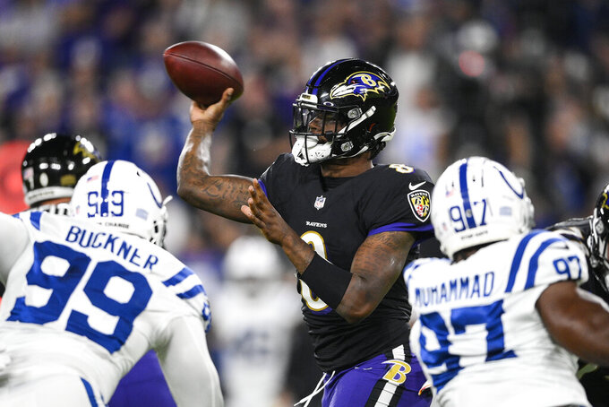 Baltimore Ravens quarterback Lamar Jackson (8) throws the ball under pressure from Indianapolis Colts defensive tackle DeForest Buckner (99) and defensive end Al-Quadin Muhammad (97) during the first half of an NFL football game, Monday, Oct. 11, 2021, in Baltimore. (AP Photo/Nick Wass)