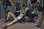 A reporter falls after being sprayed with pepper spray by police during a protest in Causeway Bay during the annual handover march in Hong Kong, Wednesday, July. 1, 2020. Hong Kong marked the 23rd anniversary of its handover to China in 1997, one day after China enacted a national security law that cracks down on protests in the territory. (AP Photo/Vincent Yu)