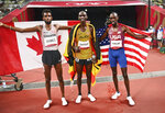 Joshua Cheptegei, center, of Uganda poses after winning gold alongside silver medalist Mohammed Ahmed, left, of Canada and bronze medalist Paul Chelimo of the United States after the final of the men's 5,000-meters at the 2020 Summer Olympics, Friday, Aug. 6, 2021, in Tokyo. (Dylan Martinez/Pool Photo via AP)