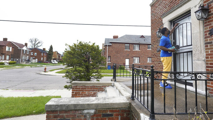 Robert Day knocks on a door before leaving a flyer on a home in Detroit, Tuesday, May 4, 2021. Officials are walking door-to-door to encourage residents of the majority Black city to get vaccinated against COVID-19 as the city's immunization rate lags well behind the rest of Michigan and the United States. (AP Photo/Paul Sancya)