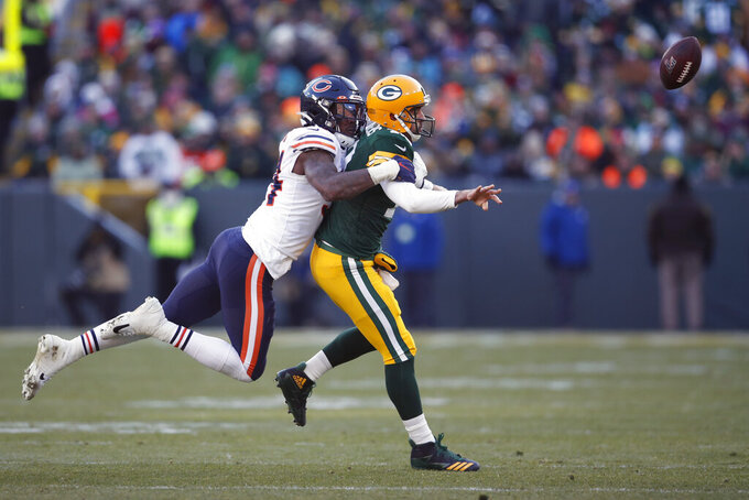 FILE - In this Dec. 15, 2019, file photo, Green Bay Packers quarterback Aaron Rodgers (12) tries to avoid Chicago Bears outside linebacker Leonard Floyd (94) during an NFL football game in Green Bay, Wis. Floyd moved from Chicago to Los Angeles for the chance to realize his full potential as a pass rusher with the Rams. (AP Photo/Jeff Haynes, File)