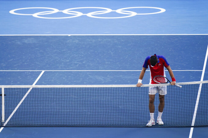 Novak Djokovic, of Serbia, reacts after being defeated by Pablo Carreno Busta, of Spain, in the bronze medal match of the tennis competition at the 2020 Summer Olympics, Saturday, July 31, 2021, in Tokyo, Japan. (AP Photo/Seth Wenig)