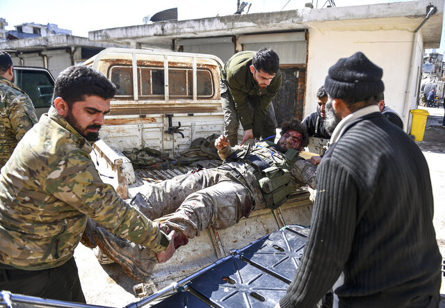 In this photo taken on Sunday, March 1, 2020, Turkey-backed opposition fighters transport a fellow fighter for treatment after he was wounded in fighting with Syrian government forces and their allies in Sarmin, south of Idlib, Syria. Fighting on the ground in Idlib continued Monday, with heavy clashes between Syrian government forces and Turkish-backed fighters. (AP Photo)