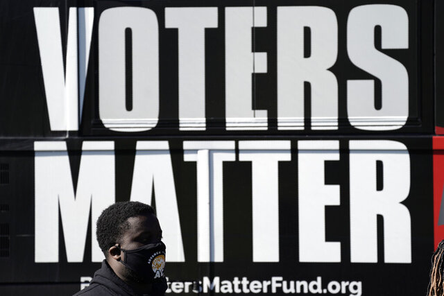 In this Nov. 3, 2020, photo, a man wearing a mask gathers with a group in support of Black Voters Matter at the Graham Civic Center polling site in Graham, N.C. Even as votes are still tallied, there's little dispute that Black voters were a driving national force pushing the former vice president to the winner's column. (AP Photo/Gerry Broome)
