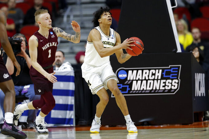 Michigan guard Eli Brooks drives to the basket ahead of Montana guard Timmy Falls, left, during a first round men's college basketball game in the NCAA Tournament, Thursday, March 21, 2019, in Des Moines, Iowa. (AP Photo/Charlie Neibergall)