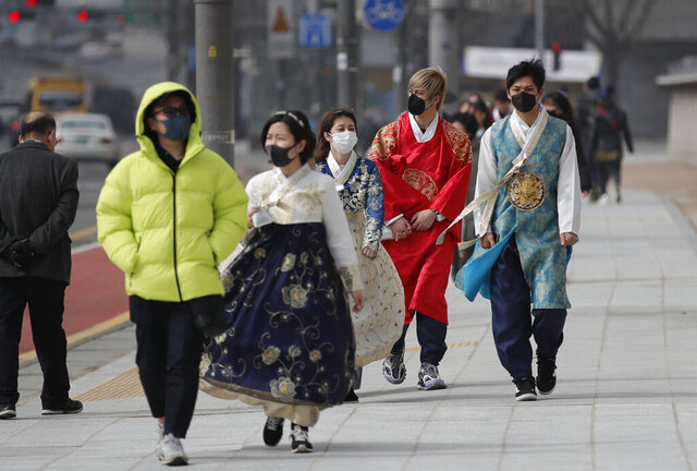 REMOVES REFERENCE TO NUMBER OF VIRAL INFECTIONS - Visitors wearing face masks walk near the Gwanghwamun, the main gate of the 14th-century Gyeongbok Palace, and one of South Korea's well-known landmarks, in Seoul, South Korea, Saturday, Feb. 22, 2020.  South Korea's Vice Health Minister Kim Gang-lip says the outbreak has entered a serious new phase but expressed cautious optimism that it can be contained to the region surrounding Daegu, where the first case was reported on Tuesday. (AP Photo/Lee Jin-man)