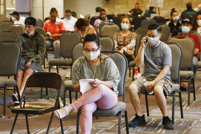 FILE - People wait to speak with representatives from the Oklahoma Employment Security Commission about unemployment claims Thursday, July 9, 2020, in Midwest City, Okla. Stark evidence of the damage the resurgent viral outbreak has caused the U.S. economy could come Friday, Aug. 7,  when the government is expected to report that the pace of hiring has slowed significantly after a brief rebound in the spring. (AP Photo/Sue Ogrocki)