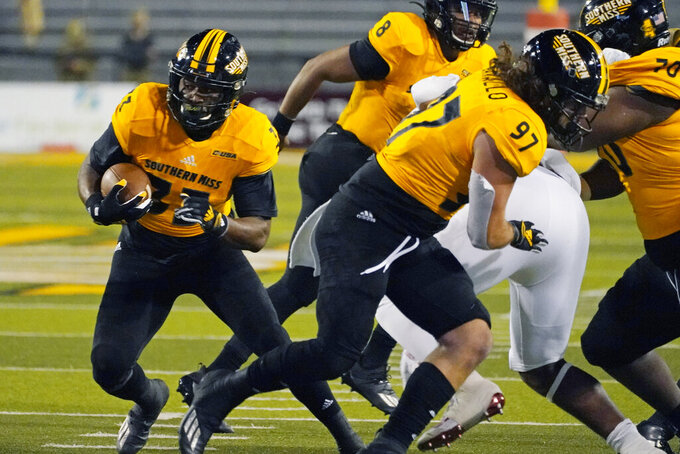 Southern Mississippi running back Kevin Perkins (33) follow the block of tight end Cole Cavallo (97) for a short gain during the first half of the team's NCAA college football game against Florida Atlantic, Thursday, Dec. 10, 2020, in Hattiesburg, Miss. (AP Photo/Rogelio V. Solis)
