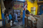 Election officers walk past a barber shop carrying electronic voting machines at the end of polling in Varanasi, India, Sunday, May 19, 2019. Indians voted in the seventh and final phase of national elections, wrapping up a 6-week-long long, grueling campaign season with Prime Minister Narendra Modi's Hindu nationalist party seeking reelection for another five years. Counting of votes is scheduled for May 23. (AP Photo/Rajesh Kumar Singh)