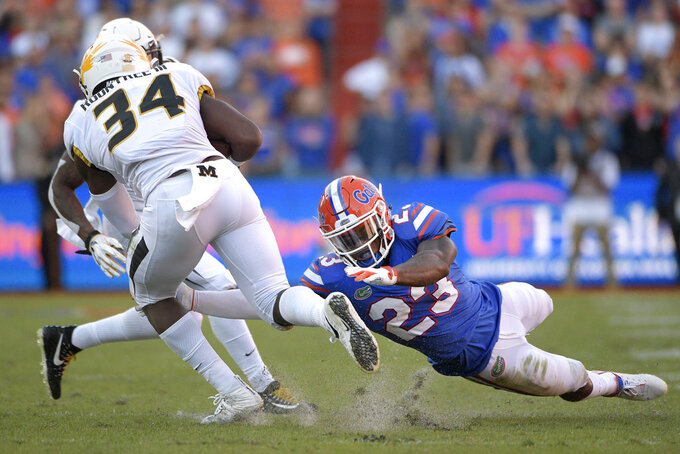 Missouri running back Larry Rountree III (34) is tripped by Florida defensive back Chauncey Gardner-Johnson (23) after catching a pass during the first half of an NCAA college football game Saturday, Nov. 3, 2018, in Gainesville, Fla. (AP Photo/Phelan M. Ebenhack)
