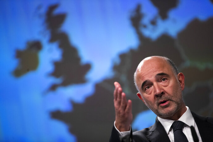 European Commissioner for Economic and Financial Affairs Pierre Moscovici talks to journalists during a news conference at the European Commission headquarters in Brussels, Thursday, Nov. 7, 2019. The European Union's executive branch has cut its growth forecasts for the 19-country eurozone for this year and next and warned that conditions could worsen in the face of an array of uncertainties. (AP Photo/Francisco Seco)