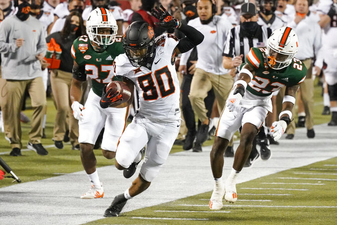 Oklahoma State wide receiver Brennan Presley (80) steps out of bounds after a reception in front of Miami safety Brian Balom (27) and cornerback Te'Cory Couch (23) during the first half of the Cheez-it Bowl NCAA college football game, Tuesday, Dec. 29, 2020, in Orlando, Fla. (AP Photo/John Raoux)