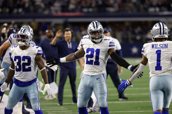 Dallas Cowboys' Corey Clement (32), Ezekiel Elliott (21) and Cedrick Wilson (1) celebrate late in the second half of an NFL football game against the Philadelphia Eagles in Arlington, Texas, Monday, Sept. 27, 2021. (AP Photo/Ron Jenkins)