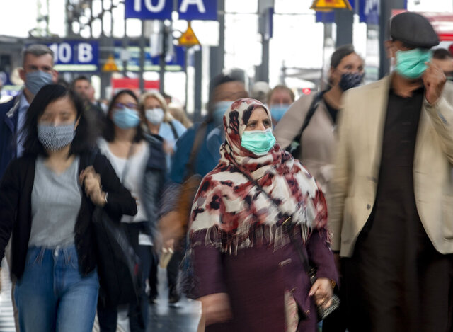 People wear face masks as they leave a train at the central train station in Frankfurt, Germany, Thursday, June 18, 2020. (AP Photo/Michael Probst)