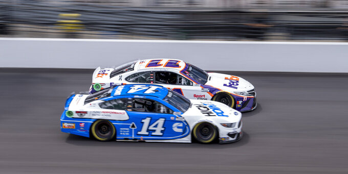 Chase Briscoe (14) and Denny Hamlin (11) battle for track position during a restart of a NASCAR Cup Series auto race at Indianapolis Motor Speedway, Sunday, Aug. 15, 2021, in Indianapolis. (AP Photo/Doug McSchooler)