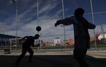 In this Jan. 18, 2020 photo, youths are silhouetted as they play with soccer ball at a sports complex in El Alto, Bolivia. In 2007, former President Evo Morales launched a program called