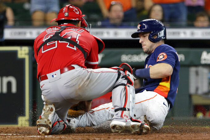 Houston Astros' Alex Bregman, right, is out at the plate on the throw to Los Angeles Angels catcher Kurt Suzuki, left, on the single by Yuli Gurriel during the seventh inning of a baseball game Sunday, Sept. 12, 2021, in Houston. (AP Photo/Michael Wyke)