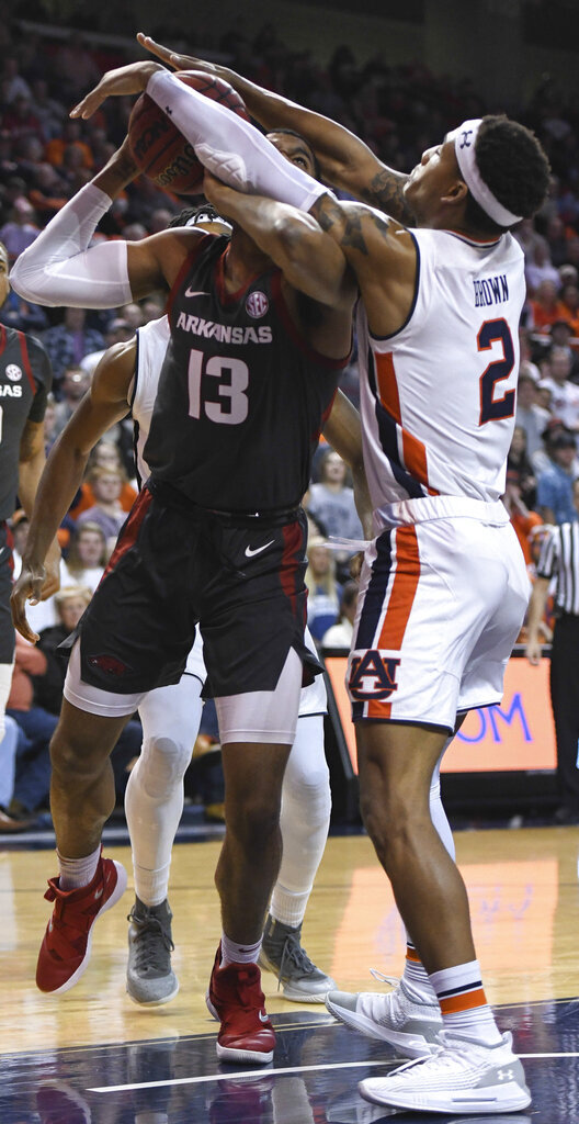 Auburn guard Bryce Brown (2) fouls Arkansas guard Mason Jones (13) during the first half of an NCAA college basketball game Wednesday, Feb. 20, 2019, in Auburn, Ala. (AP Photo/Julie Bennett)