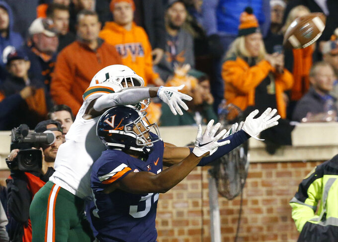 Virginia cornerback Bryce Hall (34) looks to intercept a pass intended for Miami wide receiver Mark Pope, left, during the second half of an NCAA college football game in Charlottesville, Va., Saturday, Oct. 13, 2018. Virginia defeated Miami 16-13. Hall dropped the ball. (AP Photo/Steve Helber)