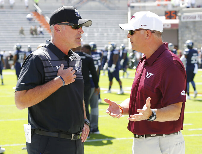 FILE - In this Sept. 23, 2017, file photo, Old Dominion head coach Bobby Wilder, left, greets Virginia Tech head coach Justin Fuente prior to the start of an NCAA college football game in Blacksburg, Va. Bobby Wilder and the Monarchs are excited about their rare opportunity to host at Top 25 program. No. 13 Virginia Tech makes the instate trek to the Tidewater area on Saturday. (AP Photo/Steve Helber, File)