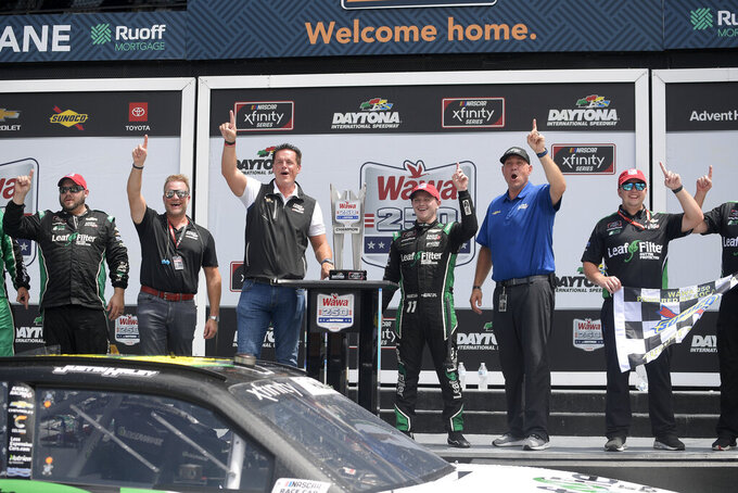 Justin Haley (11) celebrates in victory lane with team owner Matt Kaulig, at left of the trophy, and team members after a NASCAR Xfinity Series auto race at Daytona International Speedway, Saturday, Aug. 28, 2021, in Daytona Beach, Fla. (AP Photo/Phelan M. Ebenhack)