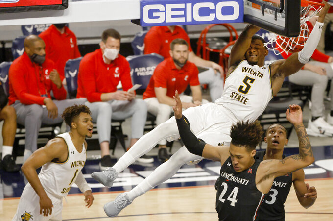 Wichita State forward Trey Wade (5) slam dunks over Cincinnati's Jeremiah Davenport (24) and Mika Adams-Woods (23) as Wichita State guard Tyson Etienne (1) reacts during the first half of an NCAA college basketball game in the semifinal round of the American Athletic Conference men's tournament Saturday, March 13, 2021, in Fort Worth, Texas. (AP Photo/Ron Jenkins)
