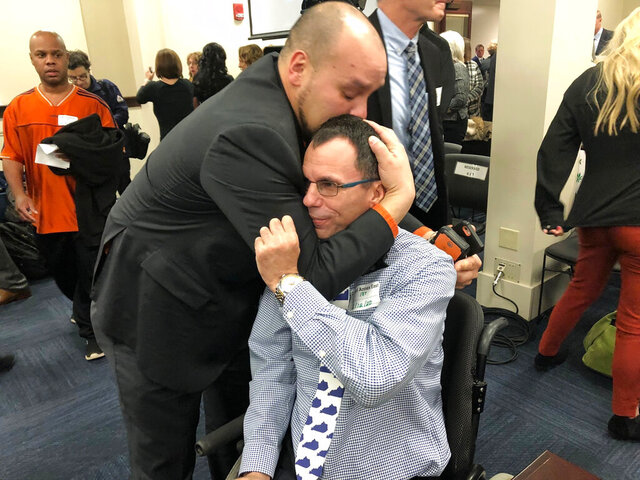 In this Wednesday, Feb. 12, 2020, photo, Eric Crawford, center right, is hugged by another medical marijuana advocate after a bill to legalize medical cannabis in Kentucky was approved by a state House committee, in Frankfort, Ky. Kentucky House Speaker David Osborne said Friday that the bill could possibly come up for a House vote as soon as next week. (AP Photo/Bruce Schreiner)