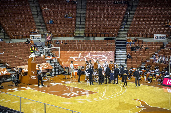 Texas players meet during a timeout in the team's NCAA college basketball game against Texas-Rio Grande Valley on Wednesday Nov. 25, 2020, in Austin, Texas. (Ricardo B. Brazziell/Austin American-Statesman via AP)