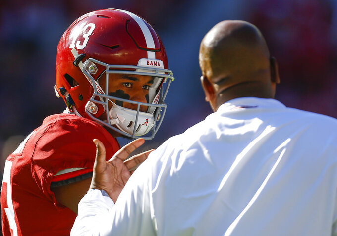 Alabama quarterback Tua Tagovailoa (13) talks with offensive coordinator Mike Locksley before an NCAA college football game against Mississippi State, Saturday, Nov. 10, 2018, in Tuscaloosa, Ala. (AP Photo/Butch Dill)