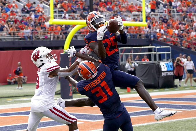 Illinois defensive back Kerby Joseph (25) intercepts a pass intended for Wisconsin wide receiver Kendric Pryor (3) as Devon Witherspoon also defends during the first half of an NCAA college football game Saturday, Oct. 9, 2021, in Champaign, Ill. (AP Photo/Charles Rex Arbogast)