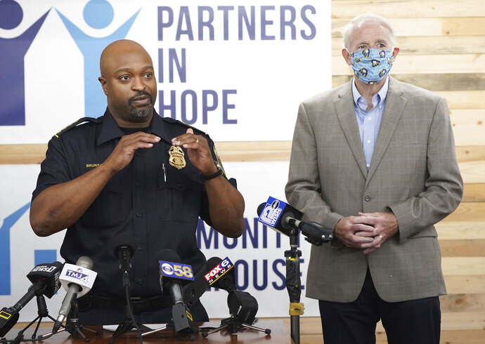 Acting Milwaukee Police Chief Michael Brunson, left, talks as Mayor Tom Barrett looks on during a press conference announcing a new Milwaukee Police Department-led initiative to improve police-community relations,  at the Community Warehouse, in Milwaukee on Wednesday, Aug. 12, 2020. While voters physically headed to the polls for Tuesday's primary election, many chose to vote absentee due to the Covid pandemic. (Mike De Sisti/Milwaukee Journal-Sentinel via AP)