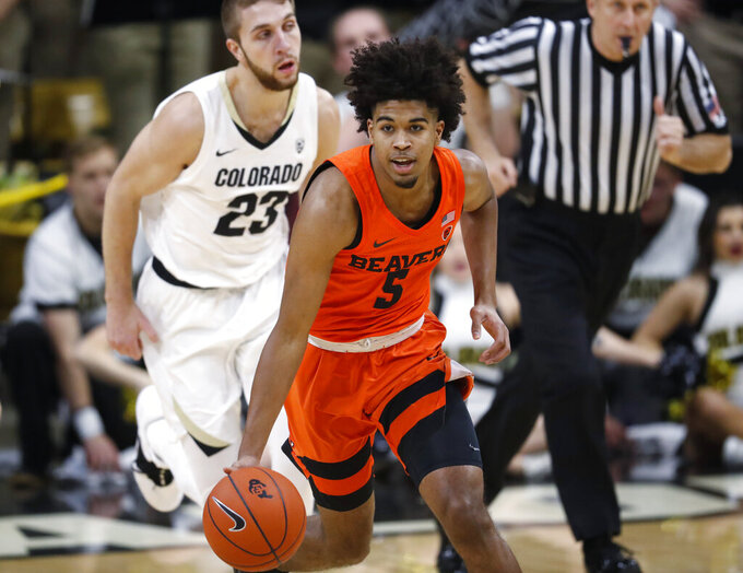 Oregon State guard Ethan Thompson, front, picks up the ball as Colorado forward Lucas Siewert follows in the first half of an NCAA college basketball game Thursday, Jan. 31, 2019, in Boulder, Colo. (AP Photo/David Zalubowski)