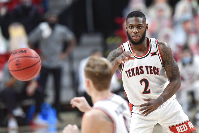 Texas Tech's Jamarius Burton (2) passes the ball to Mac McClung (0) during the first half of an NCAA college basketball game against Kansas in Lubbock, Texas, Thursday, Dec. 17, 2020. (AP Photo/Justin Rex)