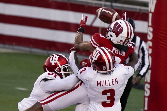 Indiana defensive back Tiawan Mullen (3)and defensive back Bryant Fitzgerald (31) break up a pass intended for Wisconsin's Kendric Pryor during the first half of an NCAA college football game Saturday, Dec. 5, 2020, in Madison, Wis. (AP Photo/Morry Gash)