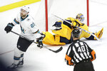 Nashville Predators goaltender Juuse Saros, of Finland, falls to the ice after stopping a penalty shot by San Jose Sharks center Barclay Goodrow (23) in the third period of an NHL hockey game Tuesday, Dec. 10, 2019, in Nashville, Tenn. (AP Photo/Mark Humphrey)