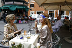 A woman sips her coffee from under her facial protection at a cafe with outdoor tables in Rome Monday, May 18, 2020. Italy is slowly lifting restrictions after a two-month coronavirus lockdown. (Cecilia Fabiano /LaPresse via AP)