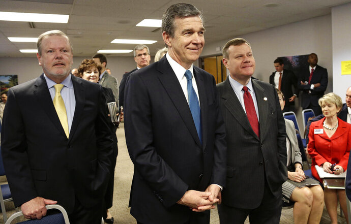 FILE - In this May 1, 2018, file photo, from left, Senate President Pro Tempore Phil Berger, North Carolina Gov. Roy Cooper and House Speaker Tim Moore pause prior to a news conference in Raleigh, N.C.  The North Carolina General Assembly could soon be done wrestling with legislation this year, but that doesn't mean they'll pin down a broad budget law or path forward on Medicaid expansion. Lawmakers return on Monday, Oct. 21, 2019 following a 10-day break. Senate leader Phil Berger says his chamber will be done with regular business by Oct. 31. House Speaker Tim Moore hasn't committed publicly to that date, but it's clear the end is near. (AP Photo/Gerry Broome, File)