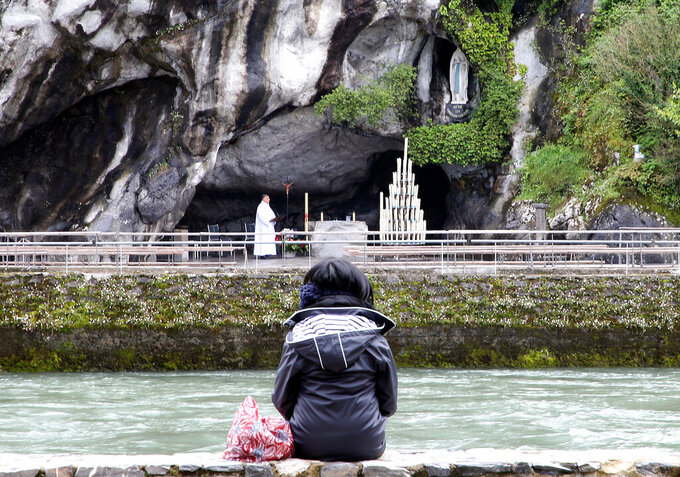 A pilgrim prays in front of the Roman Catholic shrine at Lourdes, in southwestern France, Saturday, May 16, 2020, after being closed on March 17 for the first time in its history following the coronavirus pandemic. The COVID-19 pandemic emptied out churches and also forced the cancellation of the Lourdes pilgrimage. (AP Photo/Bob Edme)