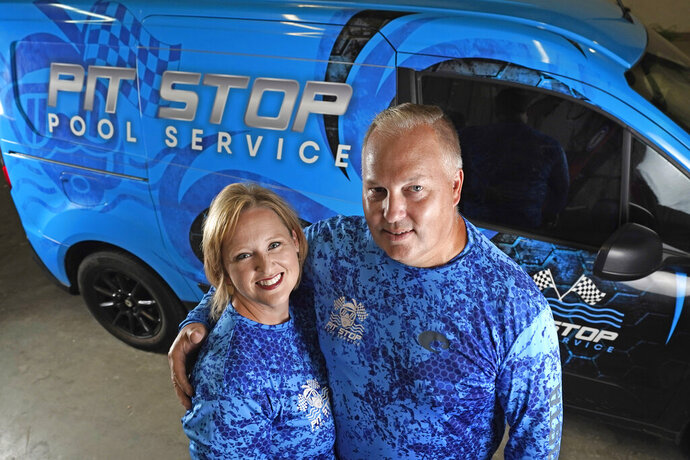 Amy and Cody Morgan pose in their new warehouse, Friday, Sept. 4, 2020, in Cypress, Texas. The couple, who lost their jobs as corporate executives during the coronavirus pandemic, decided to start a pool servicing company, Pit Stop Pools. (AP Photo/David J. Phillip)