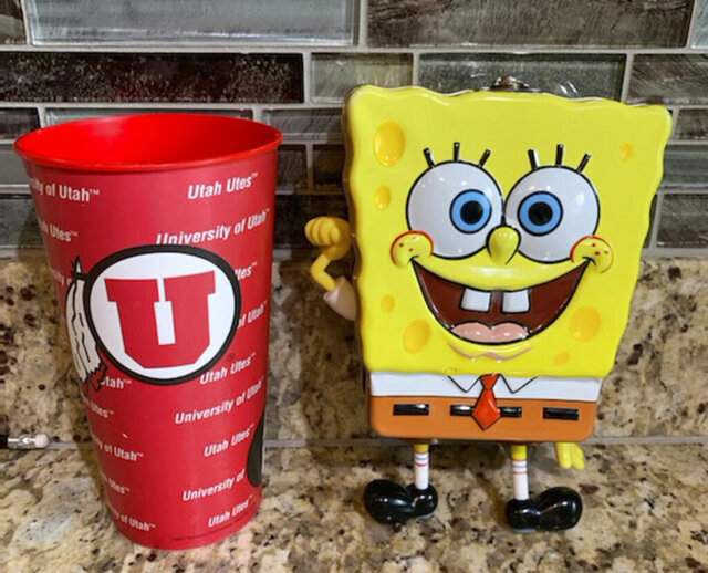 In this photo provided by Utah sports writer Andy Larsen are a childhood piggybank, right, and a plastic cup on Tuesday, Nov. 24, 2020, in Salt Lake City. Larsen's spontaneous tweet looking for someone in need to whom he could give the $185 he had in the two items quickly snowballed into tens of thousands of dollars in donations from strangers, as well as messages from people who could use the help. (Andy Larsen via AP)